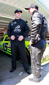 Yates Racing teammates Travis Kvapil (left) and David Gilliland compare notes after practice for the Subway Fresh Fit 500 at Phoenix International Raceway. (Photo Credit: John Harrelson/Getty Images for NASCAR)