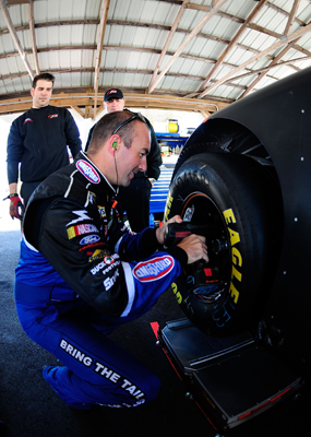 Marcos Ambrose helps his No. 47 crew by working on his tires on Wednesday during the NASCAR Sprint Cup Series test at Pocono Raceway. (Photo Credit: Rusty Jarrett/Getty Images for NASCAR)