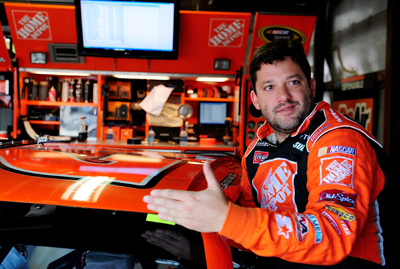 Tony Stewart climbs in his car to practice for the LifeLock 400 at Michigan International Speedway. (Photo Credit: Rusty Jarrett/Getty Images for NASCAR)