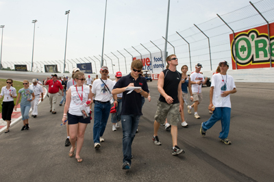 Landon Cassill (L), a native of Cedar Rapids, Ia., and Carl Edwards, who is from Columbia, Mo., lead fans on a charity track walk Saturday at Gateway. Proceeds from the event went to the American Red Cross and its outreach to Midwest flood victims. (Photo Credit: Padraic Major for NASCAR)