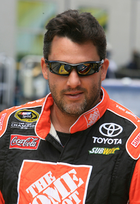 Tony Stewart is all smiles in the garage after unveiling his new car number and sponsors at Indianapolis Motor Speedway. (Photo Credit: Jerry Markland/Getty Images for NASCAR)