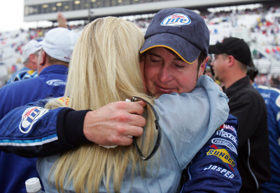 Kurt Busch hugs wife Eva after the Lenox Industrial Tools 301 NASCAR Sprint Cup Series race was declared official on Sunday at New Hampshire Motor Speedway. (Photo Credit: Jim McIsaac/Getty Images)