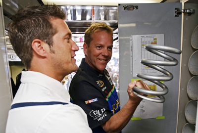 J.J. Yeley (L), driver of the #96 DLP HDTV Toyota, shows actor Kiefer Sutherland (R) a car spring and the inside of the hauler during the NASCAR Sprint Cup Series Sunoco Red Cross Pennsylvania 500 at the Pocono Raceway on August 3, 2008 in Long Pond, Pennsylvania. (Photo by Drew Hallowell/Getty Images for NASCAR)