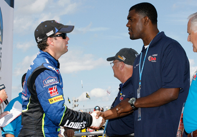 Jimmie Johnson, driver of the No. 48 Lowe's Chevrolet (L) greets grand marshal and former Buffalo Bills tight end Kevin Everett prior to the NASCAR Nationwide Series Zippo 200 at the Watkins Glen International on August 9, 2008 in Watkins Glen, N.Y. (Photo Credit: Geoff Burke/Getty Images for NASCAR)