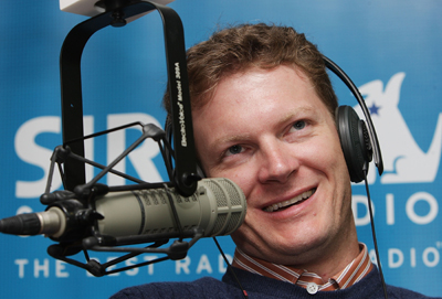 Dale Earnhardt Jr. smiles while chatting with David Poole and Mike Bagley on The Morning Drive on Sirius XM Radio. (Photo Credit: Mike Stobe/Getty Images for NASCAR)