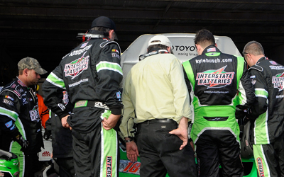Kyle Busch and the crew of the #18 Interstate Batteries Toyota look at the car in the garage area during the NASCAR Sprint Cup Series Camping World RV 400 at Dover International Speedway on September 21, 2008 in Dover, Delaware. (Photo by Grant Halverson/Getty Images for NASCAR)