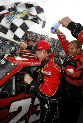 Johnny Benson and his crew celebrate winning the Kroger 200 at Martinsville Speedway. The win moved Benson into first place in the point standings ahead of Ron Hornaday Jr. (Photo Credit: Jason Smith/Getty Images for NASCAR)