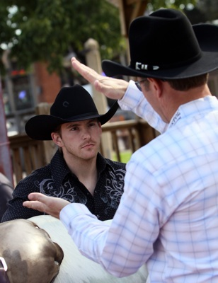 Former four-time bull riding champion Tuff Hedeman (right) gives NASCAR Sprint Cup Series driver Scott Speed (left) some bull riding tips in the Fort Worth Stockyards Tuesday, October 21, 2008.  (Photo By Tom Pennington/Getty Images for the Texas Motor Speedway)