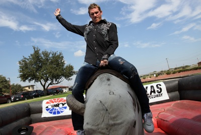 NASCAR Sprint Cup Series driver Scott Speed (right) hangs on during his maiden ride on a mechanical bull in the Fort Worth Stockyards Tuesday, October 21, 2008. (Photo By Tom Pennington/Getty Images for the Texas Motor Speedway)