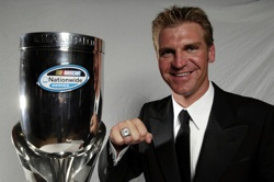 2008 NASCAR Nationwide Series champion driver Clint Bowyer shows off his championship ring and trophy. (Photo Credit: Marc Serota/Getty Images for NASCAR)