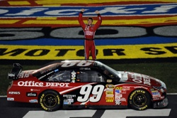 Carl Edwards salutes the fans before doing his trademark back flip after winning Sunday's Dickies 500 at Texas Motor Speedway. The win was Edwards eighth for the 2008 season. (Photo Credit: Ronald Martinez/Getty Images)