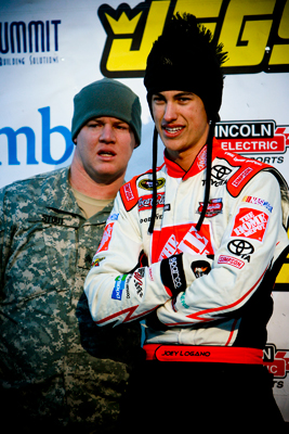 Joey Logano and brakeman Kenneth Stout, who led with only Todd Bodine left to go, watch the TV at the finish line as the eventual champion makes his final run. (Photo Credit: Todd Bissonette)