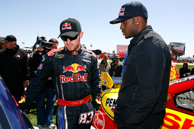 (Left to right) NASCAR Sprint Cup Series driver Brian Vickers talks about his No. 83 Red Bull Toyota with New Orleans Saints running back Reggie Bush before Sunday's Samsung 500 at Texas Motor Speedway in Fort Worth, Texas. (Photo Credit: Jason Smith/Getty Images for NASCAR)