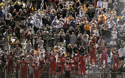 The crew members of Tony Stewart's No. 14 Office Depot Chevrolet climb the fence to salute the fans after winning the NASCAR Sprint All-Star Race at Lowe's Motor Speedway. (Photo Credit: Drew Hallowell/Getty Images for NASCAR)