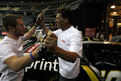 (Left to right) NASCAR Sprint Cup Series drivers Brian Vickers and Michael Waltrip celebrate winning the Media Pit Crew Challenge after pushing their car across the finish line Wednesday at Time Warner Cable Arena in Charlotte, N.C. (Photo Credit: Streeter Lecka/Getty Images for NASCAR)