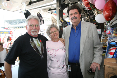 (Right to left) NASCAR President Mike Helton congratulates Brenda and Danny Barrett on their 15th anniversary on Saturday, where they were married, at Darlington Raceway. The Barretts drive the Official NASCAR Merchandise Trailer. (Photo Credit: Jerry Markland/Getty Images for NASCAR)