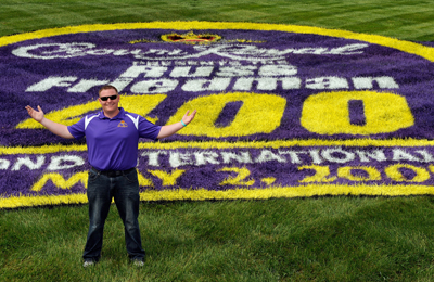 Contest winner Russ Friedman poses in front of the logo for the NASCAR Sprint Cup Series CROWN ROYAL presents The Russ Friedman 400 at Richmond International Raceway. (Photo Credit: Rusty Jarrett/Getty Images for NASCAR)