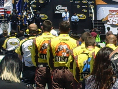 The No. 18 M&M's team listens to the invocation before the Toyota/SaveMart 350 at Infineon Raceway on Sunday, June 21, 2009 (photo credit: The Fast and the Fabulous)