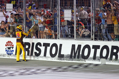 Kyle Busch gives the checkered flag to a fan after winning the Sharpie 500 at Bristol Motor Speedway. (Photo Credit: Geoff Burke/Getty Images for NASCAR)