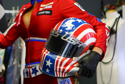 A closeup reveals the NASCAR bar logo on the chest and a NASCAR Hall of Fame logo on the left arm of 2009 Miss USA Kristen Dalton's NASCAR-themed costume for the Miss Universe Pageant. Dalton modeled the costume at Miss Universe Pageant Headquarters in New York City. (Photo Credit: Mike Stobe/Getty Images for NASCAR)