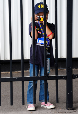 A Jimmie Johnson fan takes a picture of the NASCAR Sprint Cup Series cars as they roll out from the garage and onto the track Saturday during practice at Pocono Raceway in Long Pond, Pa. for Sunday's Sunoco Red Cross Pennsylvania 500. (Photo Credit: Rusty Jarrett/Getty Images for NASCAR)