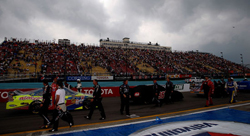 Pit crews work to cover the cars as rain postpones the start of the NASCAR Sprint Cup Series Heluva Good! Sour Cream Dips at Watkins Glen International on Sunday in Watkins Glen, N.Y. The race has been rescheduled for noon ET Monday on ESPN, MRN, SIRIUS Satellite Radio. (Photo credit: Chris Graythen/Getty Images)