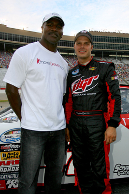NASCAR Nationwide team co-owner Evander Holyfield (left) and David Gilliland (right), driver of the No. 42 moveforever.com/arthritis.org Dodge stand on pit road before Saturday's start of the NASCAR Nationwide Series Degree V12 300 at Atlanta Motor Speedway. (Photo Credit: Jason Smith/Getty Images)