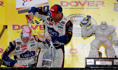 Mechanic Joe Claridge gives Jimmie Johnson a beer bath in Victory Lane after his win in the AAA 400 at Dover International Speedway. (Photo Credit: Jeff Zelevansky/Getty Images)