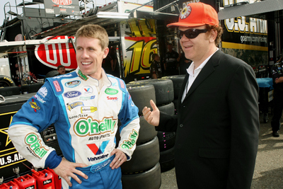 (Right to left) Actor John C. Reilly, and NASCAR Nationwide Series Copart 300 Grand Marshal, talks with NASCAR driver Carl Edwards at Edwards' hauler before the race at Auto Club Speedway on Saturday in Fontana, Calif. (Photo Credit: Stephen Dunn/Getty Images for NASCAR)