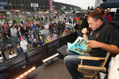 NASCAR Sprint Cup Series driver of the No. 39 Chevrolet Ryan Newman reads a book to children in the FanZone as part of