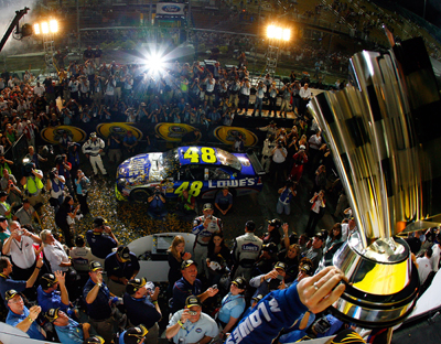 Hendrick Motorsports teammates look on as Jimmie Johnson hoists the Sprint Cup trophy for the fourth consecutive season. (Photo Credit: Rusty Jarrett/Getty Images for NASCAR)