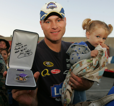 (Left to right) Joshua Deering and his daughter Kaydence display his Purple Heart, signed by Jimmie Johnson, four-time NASCAR Sprint Cup Series campion, at Camp Pendelton on Monday in Oceanside, Calif. (Photo Credit: Todd Warshaw/Getty Images for NASCAR)