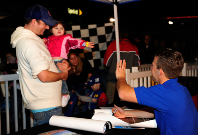NASCAR Sprint Cup Series driver AJ Allmendinger waves to a young fan Friday in Daytona Beach, Fla. at the NASCAR Preseason Thunder Fan Fest at Daytona International Speedway. (Credit: Rusty Jarrett/Getty Images for NASCAR)