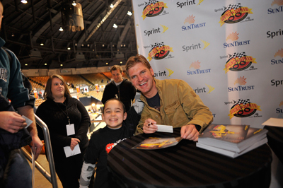 NASCAR Sprint Cup Series driver Clint Bowyer takes a picture with a young fan on Saturday during the Sprint Sound and Speed Fan Festival at Nashville Municipal Auditorium in Nashville, Tenn. (Credit: Grant Halverson/Getty Images for NASCAR)