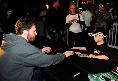 NASCAR Sprint Cup Series driver Dale Earnhardt Jr. meets a junior JR Motorsports fan Friday in Daytona Beach, Fla. at the NASCAR Preseason Thunder Fan Fest at Daytona International Speedway. (Credit: Rusty Jarrett/Getty Images for NASCAR)