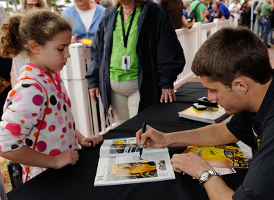A young fan gets an autograph from NASCAR Sprint Cup Series driver David Ragan on Saturday during NASCAR Preseason Thunder Fan Fest at Daytona International Speedway in Daytona Beach, FL. (Credit: Rusty Jarrett/Getty Images for NASCAR)