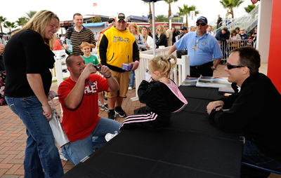 NASCAR Sprint Cup Series driver Kevin Harvick poses for a photo with a young fan during autograph sessions on Saturday at NASCAR Preseason Thunder Fan Fest at Daytona International Speedway in Daytona Beach, FL. (Credit: Rusty Jarrett/Getty Images for NASCAR)