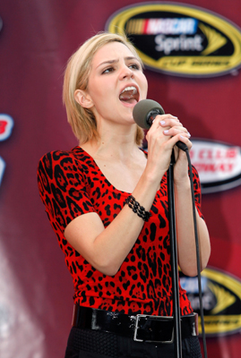 "Former ""American Idol"" runner-up and actress Katharine McPhee sings the national anthem Sunday before the start of the NASCAR Sprint Cup Series Auto Club 500 at Auto Club Speedway in Fontana, Calif. (Credit: Tom Pennington/Getty Images for NASCAR)"