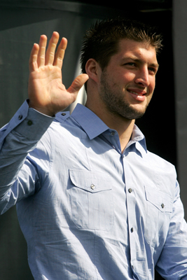 Former University of Florida quarterback Tim Tebow waves to fans in the stands before giving drivers the command to start their engines Thursday to start the first NASCAR Sprint Cup Series Gatorade Duel at Daytona International Speedway. (Credit: Jerry Markland/Getty Images for NASCAR)
