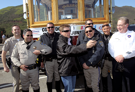 Daytona 500 champion Jamie McMurray jokes with members of the California Highway Patrol before he boarded a cable car for his victory tour of San Francisco on February 17, 2010 in San Francisco, California. (Photo by Ezra Shaw/Getty Images)