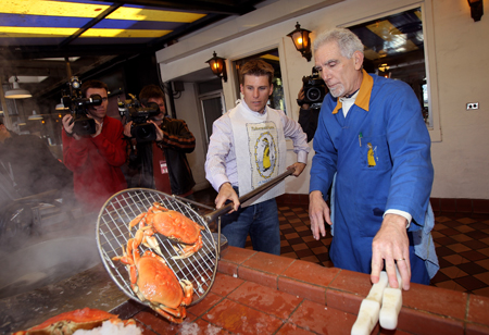 Daytona 500 champion Jamie McMurray gets lessons on how to cook and crack a crab from Anthony Geraldi, co-owner of Grotto No. 9 at Fisherman's Wharf during his victory tour of San Francisco on February 17, 2010 in San Francisco, California. (Photo by Ezra Shaw/Getty Images)