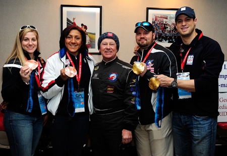 Bronze medalist members of the U.S. Olympic woman's bobsled driver Erin Pac, poses along with team brakeman Elana Meyers, NASCAR driver Geoff Bodine, head of the Bodine bobsled project, gold-winning men's bobsled team pilot Steve Holcomb and pushman Steve Mesler in the media center at Atlanta Motor Speedway. (Credit: Rusty Jarrett/Getty Images for NASCAR)