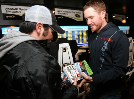 Brian Vickers congratulates Matt Dettelbach (@mdbach on Twitter) for beating him in the simulator race at the Sprint Experience. (Photo by Jerry Markland/Getty Images for NASCAR)