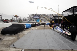 Cars sit covered on pit road during a rain shower that postponed the Goody's Fast Pain Relief 500 at Martinsville Speedway. The race will be held Monday at noon ET. (Credit: Streeter Lecka/Getty Images)