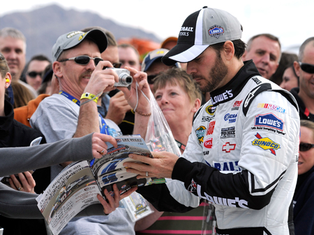 Four-time NASCAR Sprint Cup Series champion Jimmie Johnson signs autographs for fans during qualifying for the NASCAR Sprint Cup Series Shelby American at Las Vegas Motor Speedway.(Credit: John Harrelson/Getty Images)