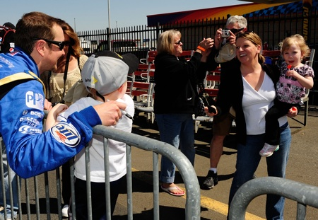 Lucky fans pose for a photo with former NASCAR Sprint Cup Series Champion Kurt Busch as he takes a break during the second day of testing in Concord, N.C. (Credit: Rusty Jarrett/Getty Images for NASCAR)