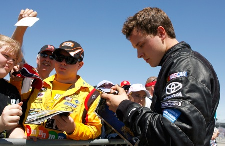 Trevor Bayne signs autographs for fans during qualifying Saturday at Nashville Superspeedway. (Credit: Jason Smith/Getty Images for NASCAR)