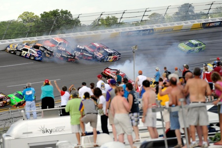 Fans look on as a 9-car accident in Turn 4 caused the Aaron's 499 at Talladega Superspeedway to go to multiple attempts at a green-white-checkered finish. (Credit: John Harrelson/Getty Images for NASCAR)