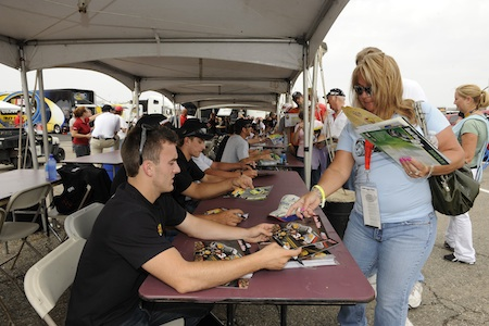 After the rain stopped on Friday at Michigan International Speedway in Brooklyn, Mich., 23 NASCAR Camping World Truck Series drivers -- including Austin Dillon (foreground) -- signed autographs for 400 fans in the Truck garage. (Credit: Rusty Jarrett/Getty Images for NASCAR)<br />
