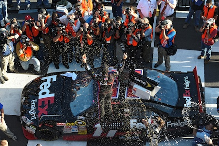 Denny Hamlin celebrates his fourth win of the season – and fourth win at Pocono Raceway – in Victory Lane. (Credit: Drew Hallowell/Getty Images for NASCAR)